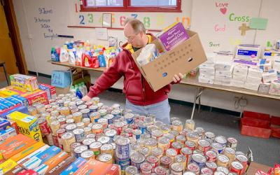 <p>Mark Messmer loads a Christmas basket with supplies for a needy family at Rochester's Peace of Christ Parish Dec. 12, 2015.  </p>