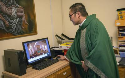 <p>Father Edison Tayag begins the YouTube live streaming of an Oct. 21 Mass at Victor&rsquo;s St. Patrick Church.  </p>