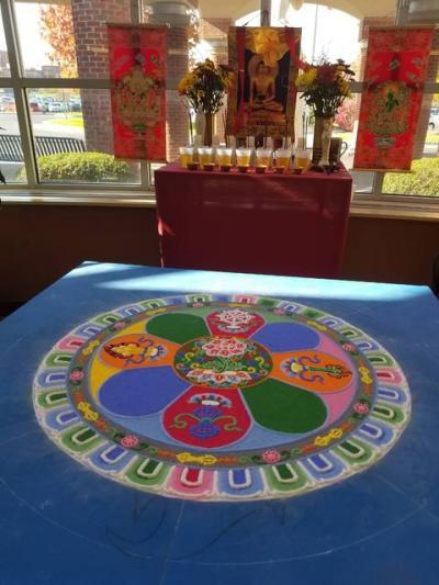 <p>The Venerable Tenzin Yignyen, a Buddhist monk and visiting professor of Tibetan Buddhism at Hobart and William Smith Colleges in Geneva, created a sand mandala in the lobby of St. Ann&rsquo;s Community in early November. (Courier photo by Annette Jiménez)