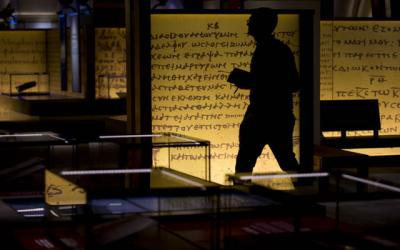 """<p>A person walks by biblical codices inside the """"History of the Bible"""" exhibit at the Museum of the Bible in Washington Nov. 15.  </p>"""