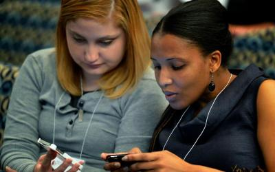 Young women tweet messages during a conference in Washington. (CNS photo by Paul Jeffrey)