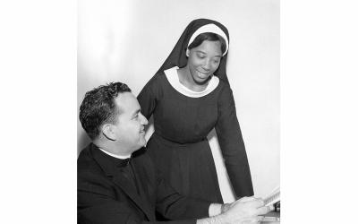 Then-Mercy Sister Martin de Porres Grey consults with a priest in an undated photo at the National Black Sisters' Conference headquarters in Washington. During the 1950s and 1960s, scores of young black Catholics desegregated the nation's all-white seminaries and convents. (CNS photo courtesy National Black Sisters')
