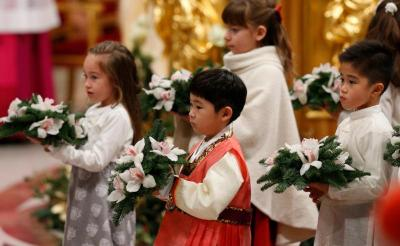 Children carry flowers in procession as Pope Francis concludes the celebration of Christmas Eve Mass in St. Peter's Basilica at the Vatican. (CNS photo by Paul Haring)