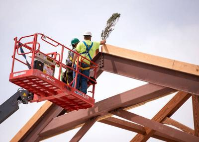 <p>Workers place a pine bough at the peak of the partially built St. Pius Tenth church in Chili Aug. 10 during a topping out ceremony. </p>