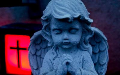 An angel statue is pictured at a grave during dusk at a cemetery in the western Austrian village of Absam Oct. 30. (CNS photo by Dominic Ebenbichler)