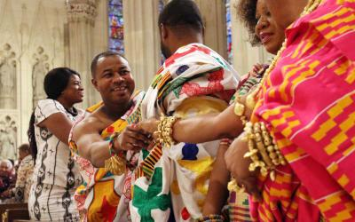 Worshippers exchange the sign of peace during the annual Black History Month Mass at St. Patrick's Cathedral in New York. Although the invitation is the same for each Mass, the way that the sign of peace is expressed can vary from parish to parish or diocese to diocese. (CNS photo by Gregory A. Shemitz)