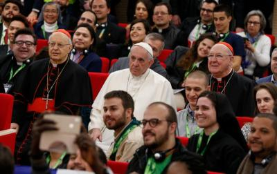 Pope Francis is pictured next to Cardinal Lorenzo Baldisseri, secretary-general of the Synod of Bishops, and Cardinal Kevin Farrell, head of the Vatican's Dicastery for Laity, the Family and Life, during a group photo at a pre-synod gathering of youth delegates in Rome March 19, 2018. The pope facilitates the work of the college of bishops in its care for the universal church by convening synods of bishops.(CNS photo by Paul Haring)
