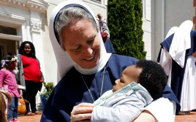Sister Mary Elizabeth, vicar general of the Sisters of Life, holds a baby during the annual Mother's Day celebration at the religious community's retreat house in Stamford, Conn.  (CNS photo by Gregory A. Shemitz)