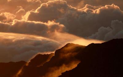 Fog and clouds are seen during sunrise over a mountain at Haleakala National Park on the Hawaiian island of Maui Oct. 9, 2018.