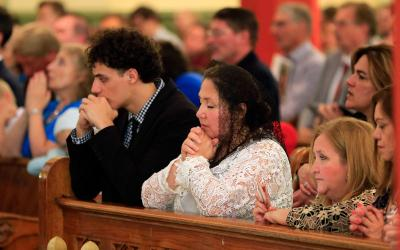 Worshippers pray during Mass. Massgoers participate through verbal responses and singing. They listen in an active, focused way to the biblical readings, and they participate through prayer that is spoken aloud with others and prayer that is quietly personal. (CNS photo/Dave Crenshaw, Eastern Oklahoma Catholic)