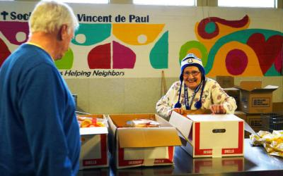 Volunteer Dee Poteet opens a new box of dessert shells to distribute to clients at the Catholic-run Indianapolis food pantry operated by the Indianapolis Council of the Society of St. Vincent de Paul.