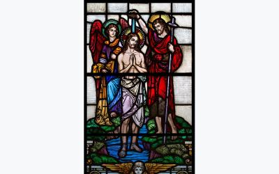 A depiction of St. John the Baptist baptizing Jesus at the Jordan River is seen in a stained-glass window at St. Paul Church in Wilmington, Del.