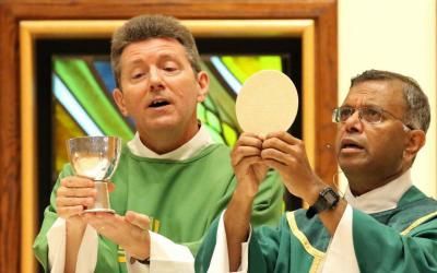 """Father Antony Asir, right, and Deacon Matthew Surico elevate the Eucharist during Mass at St. Thomas More Church in Hauppauge, N.Y. The word """"Eucharist"""" comes from the Greek word that means """"to give thanks."""" (CNS photo by Gregory A. Shemitz)"""