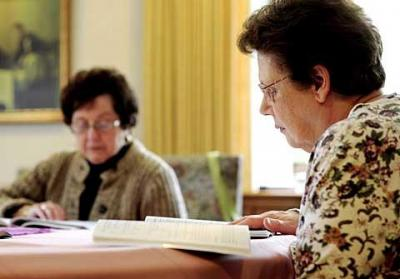 Peace of Christ parishioners Julie Morelle (left) and Joan Witner discuss a Lenten reading during a Feb. 23 meeting of the parish's Tuesday-morning small Christian community.