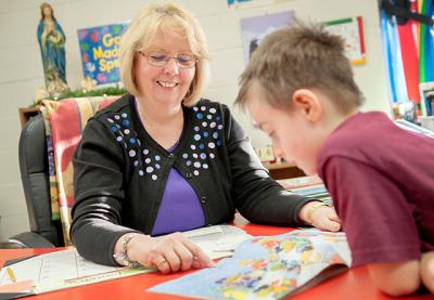 Christine Smith, a special-education resource teacher at St. Kateri School in Irondequoit, reads with kindergartner Tyler Patti Jan. 16. Each October Smith teaches a parent workshop on homework.