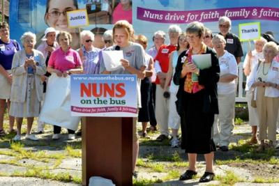 "Sister Simone Campbell (right), executive director of the Catholic social-justice lobby group NETWORK, listens to a speaker June 19 during a stopby the ""Nuns on the Bus"" tour in Dubuque, Iowa."