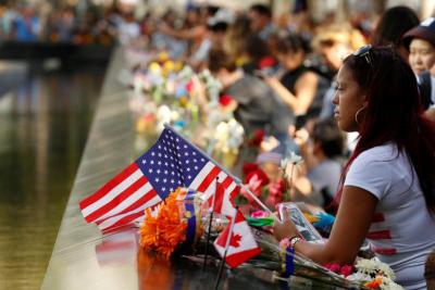 A woman holds a flag as she looks out over the National September 11 Memorial and Museum on the 15th anniversary of the 9/11 attacks in New York.