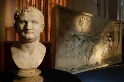 A bust of Roman Emperor Titus is pictured next to a replica of the 1st-century Arch of Titus, showing Roman soldiers carrying the menorah, in a exhibition at the Vatican May 15.