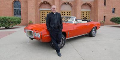 Father Matthew Keller, rector of Sacred Heart Cathedral in Gallup, N.M., poses June 8 with a 1969 Pontiac Firebird Convertible that he refurbished for a raffle in support of vocations for the Diocese of Gallup.