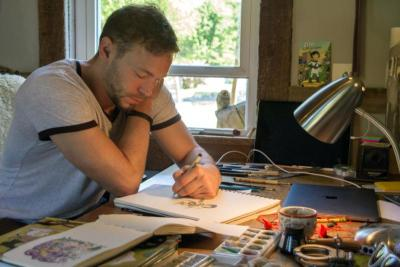 "Catholic cartoonist Ben Hatke sketches his character ""Zita the Spacegirl"" in a studio in his Front Royal, Va., home May 17. His graphic novel series features a character who was named in honor of St. Zita"