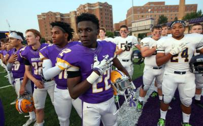 Football players from Cretin-Derham Hall High School in St. Paul, Minn., and Totino-Grace High School in Fridley, Minn., stand at midfield for the national anthem before their game Aug. 30 at the University of St. Thomas in St. Paul