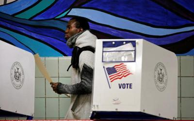 A voter carries his ballot behind a voting booth at a polling station in the Bronx section of New York City during the 2016 U.S. presidential election.