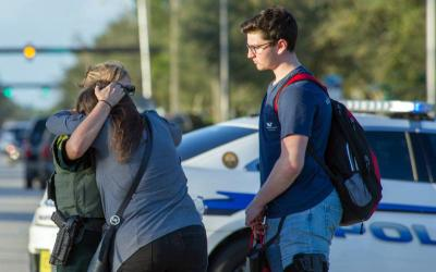 A police officer embraces a student after a shooting Feb. 14 at Marjory Stoneman Douglas High School in Parkland, Fla. At least 17 people were killed in the shooting. The suspect, 19-year-old former student Nikolas Cruz, is in custody, the sheriff said. (CNS photo by Giorgio Viera/EPA)