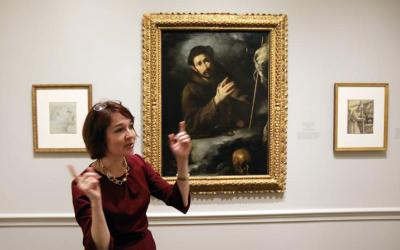 """Ginger Hammer, an assistant curator at the National Gallery of Art in Washington, gestures during a Feb. 20 media preview of the """"Heavenly Earth: Images of Saint Francis at La Verna"""" exhibit at the gallery. (CNS photo by Bob Roller)"""