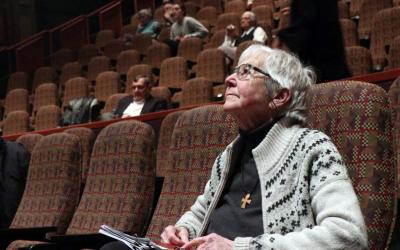 "Sister Megan Rice, a member of the Society of the Holy Child Jesus, looks up at the movie screen in the DeBartolo Performing Arts Center April 8 at the University of Notre Dame in South Bend, Ind. Sister Rice was awaiting the screening of a new documentary about her anti-nuclear activism called ""The Nuns, The Priests and The Bombs."" (CNS photo by Katie Rutter)"