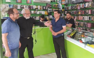 Father Emanuel Youkhana, center, meets Iraqi Christians who have opened a mobile cellphone shop in the Ninevah Plains following the defeat of the Islamic State from the area. (CNS photo courtesy CAPNI)