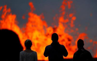 Onlookers stand on a lava flow to watch the Kilauea Volcano May 26 in the Leilani Estates near Pahoa, Hawaii. Hawaii County officials are alerting more residents in the Leilani Estates subdivision to flee fast-moving lava from Kilauea volcano. As of May 29, lava has destroyed 82 structures, including 37 homes. (CNS photo by Marco Garcia/Reuters)