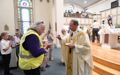 Baltimore Archbishop William E. Lori gives Communion to Kevin Marron, a Baltimore Gas and Electric employee, during a June 2 Mass at St. Paul Church in Ellicott City, Md., celebrated in solidarity with victims of recent flooding inthe historic town. (CNS photo by Richard Lippenholz, special to the Catholic Review)