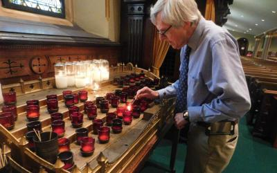 Joe Krivanek lights a candle in late June at St. Mary's Church in Albany, N.Y. (CNS photo by Emily Benson/The Evangelist)