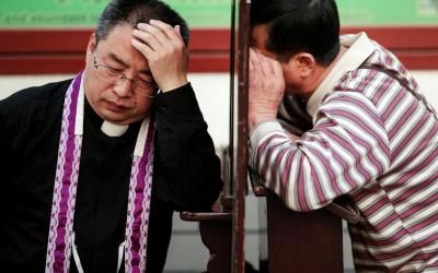 A priest hears confession on Holy Thursday, March 29, at the Cathedral of the Immaculate Conception in Beijing. (CNS photo by Damir Sagolj/Reuters)