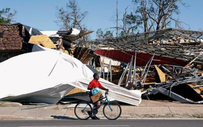 A man carries food and water past a destroyed building Oct. 13 in Parker, Fla., following Hurricane Michael. The Category 4 storm has claimed the lives of at least 19 people. (CNS photo by Terray Sylvester/Reuters)