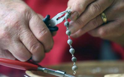 August Bueltel of St. John the Baptist in Savage, Minn., makes rosary beads Oct. 30 from his basement. (CNS photo by Dave Hrbacek/The Catholic Spirit)