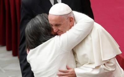 A woman embraces Pope Francis as he arrives to lead his general audience in Paul VI Hall Dec. 12 at the Vatican. (CNS photo by Max Rossi/Reuters)