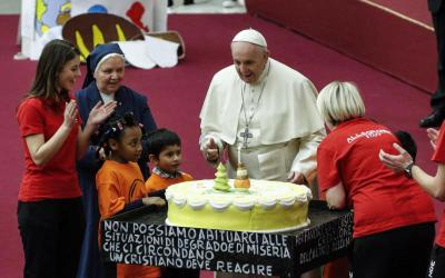 Pope Francis is presented with a cake on the eve of his 82nd birthday during a Dec. 16 audience with children and families from the Santa Marta Dispensary, a Vatican charity that offers special help to mothers and children in need. (CNS photo by Giuseppe Lami, EPA)