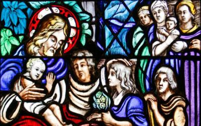Jesus welcoming children is depicted in a stained-glass window at Our Lady of Lourdes Church in Malverne, N.Y. (CNS photo/Gregory A. Shemitz)