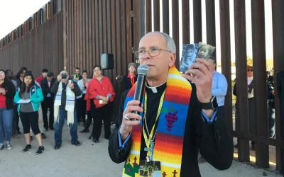 Bishop Mark J. Seitz of El Paso, Texas, holds photos of two migrant children who died in U.S. custody; he spoke during the Feb. 26 Interfaith Service for Justice and Mercy at the Border near Sunland Park, N.M. (CNS photo by David Agren)