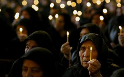 In this 2005 file photo, Bulgarian Catholic worshippers in Rakovski hold candles to mourn the death of St. John Paul II. (CNS file photo)