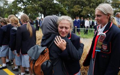 High school students embrace young Muslim women following a March 18, 2019, vigil for victims of the mosque attacks in Christchurch, New Zealand. CNS photo by Jorge Silva/Reuters)
