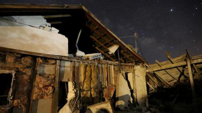 A house destroyed by an earthquake is seen at night near Trona, Calif. (CNS photo by David McNew/Reuters)