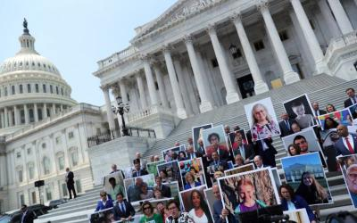 """Congressional Democrats stand outside the U.S. Capitol July 9, 2019, showing the faces of Americans they claim """"would be hurt if the Trump administration and Republicans succeed in their effort to strike down the Affordable Care Act."""" (CNS photo by Jonathan Ernst/Reuters)"""