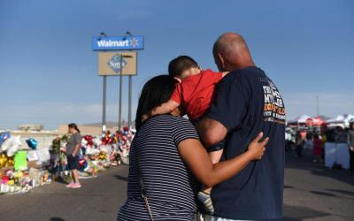 A family pays their respects Aug. 7, 2019, at a memorial four days after a mass shooting Aug. 3 at a Walmart store in El Paso, Texas. (CNS photo by Callaghan O'Hare/Reuters)