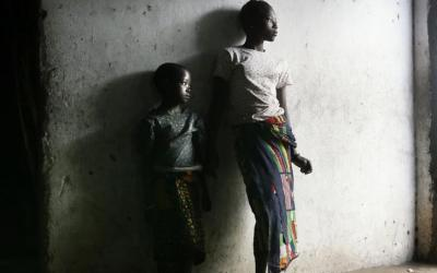 Orphaned girls, whose parents died from HIV/AIDS complications, stand inside their home in Tchemulane, Mozambique, in this 2005 file photo. (CNS photo by Stringer, Reuters)