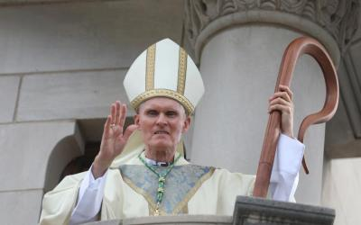 Bishop Mark E. Brennan waves from a balcony following his installation Mass Aug. 22, 2019, in the Cathedral of St. Joseph in Wheeling, W.Va.