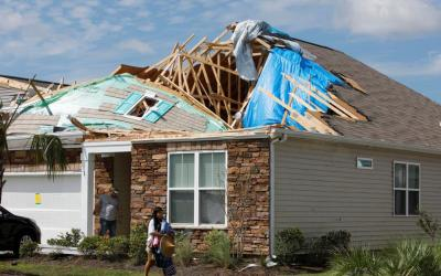 A young woman removes personal belongings from her damaged home Sept. 6, 2019, after a tornado spawned by Hurricane Dorian ripped apart her roof in Carolina Shores, N.C.