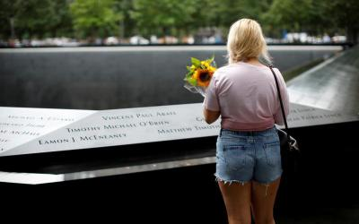 A woman holds a bouquet of flowers as she pauses at the edge of the north reflecting pool at the 9/11 Memorial and Museum in New York City Sept. 10, 2019, the eve of the 18th anniversary of the 9/11 terrorist attacks
