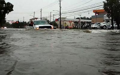 A car passes through a flooded street Sept. 19, 2019, as Tropical Storm Imelda hits Houston as seen in this screen grab obtained from social media video.